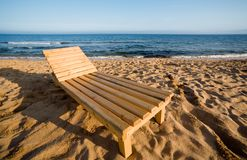 Chaise lounge & beach. Chaise lounge from a wood stands on sandy coast.Evening royalty free stock image