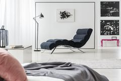 Chaise lounge and bed. Black chaise lounge lamp, art gallery and bed with a pink pillow in elegant bedroom interior stock image