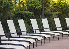 Chaise lounge chairs. Chaise lounge pool chairs lined up in a pattern Stock Photo