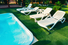 Chaise lounge chairs poolside. White plastic chaise lounge chairs on green grass poolside on sunny day stock photography