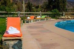 Chaise-lounge colorate dallo stagno fotografia stock libera da diritti