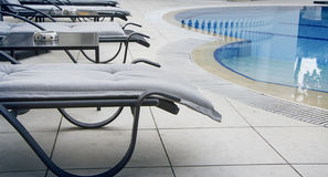 The chaise lounge costs near beautiful pool. The chaise lounge costs near beautiful swimming pool royalty free stock photo