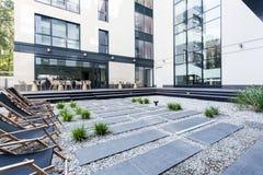 Chaise-lounge davanti alla costruzione di affari Immagini Stock Libere da Diritti