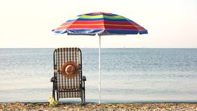Chaise lounge deck chair and umbrella. Early morning on the beach stock video
