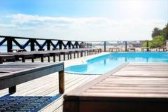 Chaise-lounge di legno del sole dallo stagno Vicino al mare fotografia stock libera da diritti