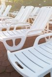Chaise-lounge di plastica bianche sui lastricatori di pietra del mattone sulla spiaggia al tramonto Il tramonto, si rilassa, vaca fotografia stock