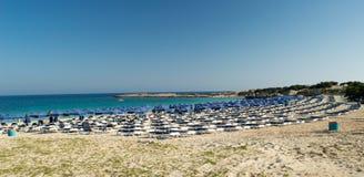 Chaise-lounge di Sun intorno alla spiaggia di Makronissos Immagine Stock