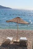 Chaise-lounge e sole di Sun sulla spiaggia fotografie stock libere da diritti