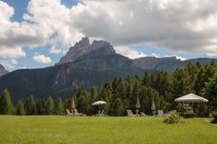 Chaise-lounge ed ombrelloni bianchi di Sun sul prato verde nel paesaggio italiano delle alpi delle dolomia Fotografia Stock