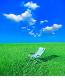 Chaise lounge on the green grass. Simple chaise lounge on the green grass royalty free stock photos