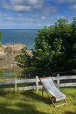 Chaise lounge on the green lawn. Excellent View of the Bay of Combe Martin. North Devon. UK royalty free stock photo