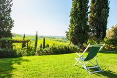 Chaise lounge on the green meadow. Tuscany, Italy stock photo