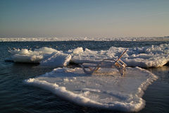 Chaise lounge on an ice floe. This photo is made in the winter, on the Black Sea, at natural lighting, in the afternoon Royalty Free Stock Image