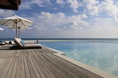 Chaise lounge with pool umbrella in the Maldives. On a tropical island stock photos