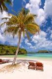 Chaise-lounge sotto una palma su una spiaggia tropicale Fotografia Stock