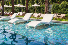 Chaise lounge  in swimming pool Stock Photo