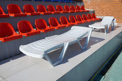 Chaise lounge in the swimming pool. Chaise lounge for fire about tribunes of the swimming pool stock photos