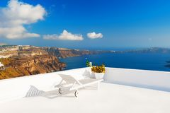 Chaise lounge on the terrace overlooking the sea. Santorini island, Greece royalty free stock photography