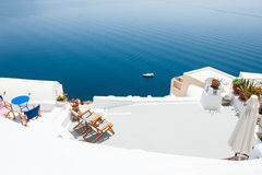 Chaise lounge on the terrace with sea view. Santorini island, Greece. Travel and vacation royalty free stock images