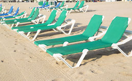 Chaise-Loungers on deserted beach in Tossa De Mar. Spain. Close-up, sunny day royalty free stock photos