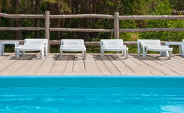 Chaise lounges around the pool Stock Photo
