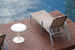 Chaise lounges around swimming pool. Outdoor Chaise lounges around swimming pool royalty free stock photo