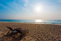 Chaise lounges on a beach. Chaise lounges on a sandy beach on the seashore royalty free stock photography