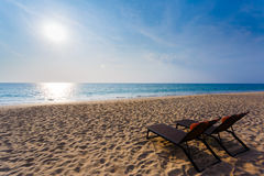 Chaise lounges on a beach. Chaise lounges on a sandy beach on the seashore stock image
