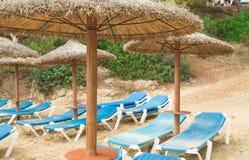Chaise Lounges och sugrörparaplyer på den härliga sandiga stranden av Palma de Mallorca royaltyfri fotografi