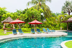 Chaise lounges at pool. In hotel in tropics stock images