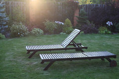 Chaise lounges at sunset. Two wooden chaise lounges in beams of the setting sun royalty free stock image