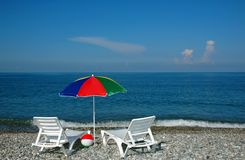 Chaise lounges and umbrella on a beach Stock Images