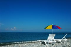 Chaise lounges and umbrella on a beach Royalty Free Stock Photo