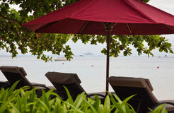 Chaise lounges and umbrella on an ocean coast. Royalty Free Stock Photography