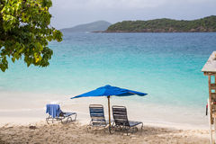 Chaise Lounges Under Blue Umbrella on Tropical Beach Stock Photos