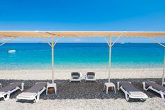 Chaise lounges on the beach in Kemer, Turkey. Chaise lounges under the tent on the pebble beach in Kemer, Turkey royalty free stock images
