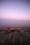 Chaise lounges on wooden pier. Photo closeup of two orange chaise lounges day beds couches standing on wooden pier against rose blue sunset light on peaceful royalty free stock photography