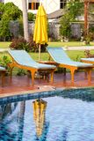 Chaise lounges and yellow umbrella next to the swimming pool, Thailand. Chaise lounges and yellow umbrella next to the swimming pool in the morning, Thailand royalty free stock images