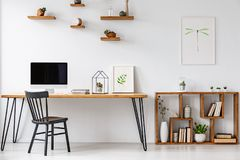 Chaise noire à la table avec le moniteur d'ordinateur dans le siège social lumineux photographie stock
