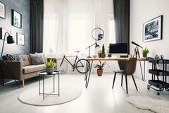 Chaise noire au bureau en bois avec l'ordinateur de bureau dans l'espace de travail dedans Images libres de droits