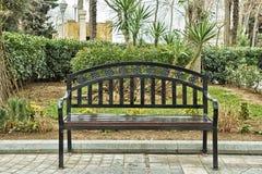 Chaise noire de fer Banc noir sur la rue Banc en parc sur un fond d'arbre de vert de brique photographie stock