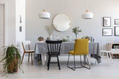 Chaise noire et jaune à la table dans l'intérieur blanc de salle à manger avec des usines, des lampes et le miroir image libre de droits