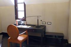 Chaise orange, bureau dans l'obscurité de chambre à coucher de grenier Photo libre de droits
