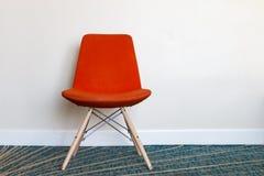 Chaise orange devant le mur léger Image libre de droits