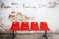 Chaise rouge dans la chambre vide contre un bri d'extérieur de bâtiments de vintage Photo stock
