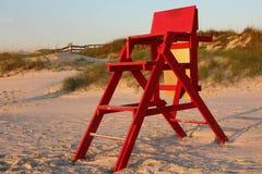 Chaise rouge de maître nageur dans le sable Photo stock