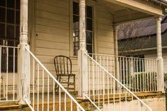 Chaise solitaire sur le porche de maison de vintage Photos stock