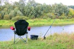 Chaise, tige et amorce de pêche sur la berge Image stock