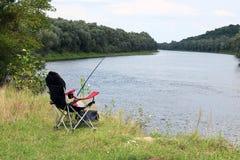 Chaise, tige et amorce de pêche sur la berge Images stock