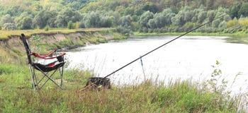 Chaise, tige et amorce de pêche sur la berge Photographie stock libre de droits